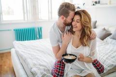 Ménages mariés heureux étant romantiques dans le lit partageant la céréale Image stock
