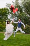 Ménages mariés heureux sautant avec les ballons rouges Photographie stock libre de droits