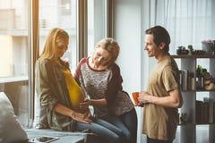 Ménages mariés joyeux passant le temps avec la femme enceinte de remplacement images stock