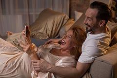 Ménages mariés joyeux riant de la vidéo sur l'instrument Photographie stock