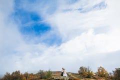 Ménages mariés nouvellement posant dans les montagnes Photo stock