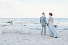Ménages mariés nouvellement tenant des mains par la mer Photographie stock