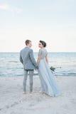 Ménages mariés nouvellement tenant des mains par la mer Images libres de droits
