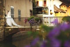 Ménages mariés romantiques heureux tenant des mains sur le vieux pont en Ann images libres de droits