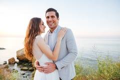 Ménages mariés romantiques se tenant et riant sur la plage Photo stock
