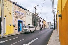 Mérida/Yucatan, Mexiko - 1. Juni 2015: Das Weinleseautoparken vor dem alten Buiding im Gegensatz zu heller gelber Farbe w Stockbilder