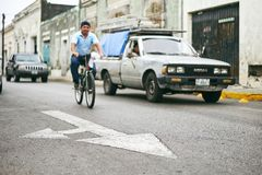 Mérida/Yucatan, Mexique - 1er juin 2015 : Le centre de la flèche se connectent la rue avec l'homme montant la bicyclette et la vo Photos libres de droits