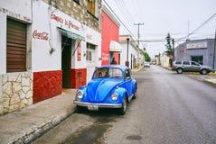 Mérida/Yucatan, Mexique - 1er juin 2015 : Le stationnement bleu de voiture de vintage devant le vieux bâtiment rouge dans Merdia, Image stock