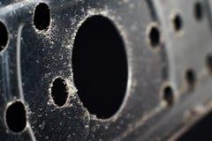 Métal argenté avec des trous sur un fond noir photographie stock libre de droits