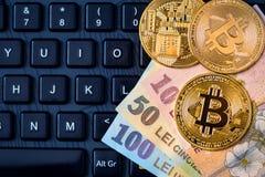 Métal Bitcoins et argent roumain Ron, nouveau Lei au-dessus du keyboa photos stock