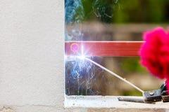 Métal et bois de soudure par l'électrode avec l'arc électrique lumineux Image stock
