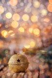 Métal Jingle Bell d'or avec l'étoile sur le Tableau en bois avec le boke et le g Photos stock