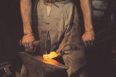 Métal travaillant de forgeron avec le marteau sur l'enclume Photos libres de droits