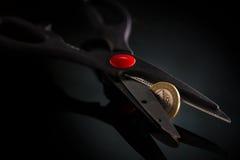 Métaphore de pièce de monnaie de devise avec des ciseaux essayant de couper Photographie stock