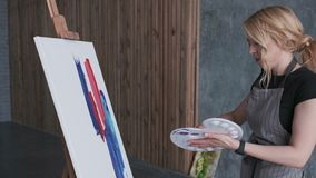 Métier de la peinture La caméra se déplace autour des artistes assez féminins tandis qu'elle peint un tableau abstrait avec de gr illustration libre de droits