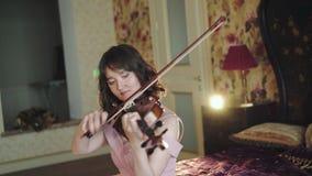 Métier musical de seulement, violoniste professionnel, s'asseyant sur le lit et le jeu banque de vidéos