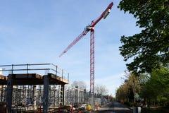 Métiers à tisser de grue de construction au-dessus de chantier de construction d'hôtel Images stock