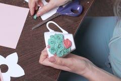 Métiers d'argile de polymère Une femme colle une fleur gommée d'argile de polymère dans une tasse Tasse décorée du stuc fait d'ar photo libre de droits