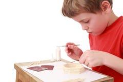 Métiers de petit garçon à la petite table, vue de côté Image stock