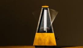 Métronome mécanique en bois avec le bras de tache floue de mouvement Images libres de droits