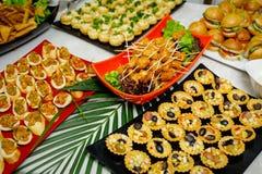 Même la table de buffet avec des festins Tartelettes de fruit, mini hamburgers, brochettes de poulet photo stock