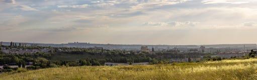 Même le paysage panoramique avec le champ, le ciel, les nuages et la ville dedans Photographie stock