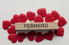 Mês de fevereiro em um retângulo de madeira e em poucos botões vermelhos da forma do coração fotos de stock royalty free