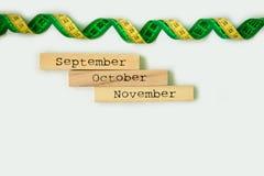 Mês de três outonos - setembro, outubro e novembro - em blocos de madeira com a fita do centímetro isolada no branco Imagem de Stock Royalty Free