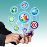 Móbil da tela de toque da mão com símbolos do negócio. Foto de Stock Royalty Free