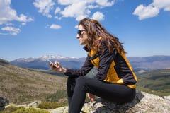 Móbil de datilografia da mulher lateral sobre a montanha Imagens de Stock