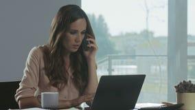 Móbil de fala da mulher de negócio Freelancer concentrado que trabalha com documentos filme