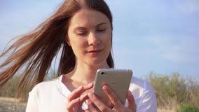Móbil do uso da mulher contra o céu azul Conversa fêmea de sorriso com os amigos através do telefone celular no movimento lento filme