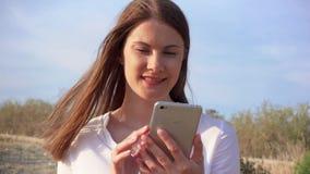 Móbil do uso da mulher contra o céu azul Conversa fêmea de sorriso com os amigos através do telefone celular no movimento lento vídeos de arquivo