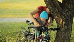 Mój macierzysty bierze opiekę piękna chłopiec w rowerowym siedzeniu w parku zbiory wideo