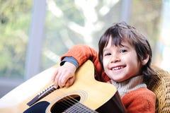 Mój syn bawić się gitarę Zdjęcie Stock