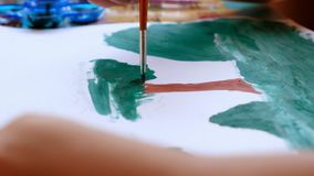 Mój syn malował drzewa, góra, trawa w obrazku który rysuje on z paletą i paintbrush zbiory wideo