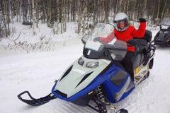 Móvil de la nieve de conducción de la muchacha en Ruka de Laponia Imagenes de archivo