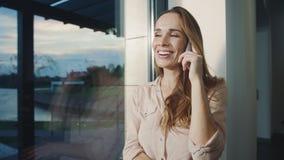 Móvil que habla de la mujer feliz en casa Retrato del teléfono de discurso sonriente de la mujer almacen de metraje de vídeo
