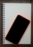Móvil, teléfono celular colocado en nootebook abierto en la tabla de madera fotos de archivo
