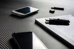 2 móviles del negocio con reflexiones y una unidad USB que miente al lado de una tableta en blanco con la unidad USB en el top, t Imágenes de archivo libres de regalías