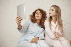 Mówi mwah kamera Dwa piękna dziewczyna siedzi w domu w nightwear ma zabawę podczas gdy brać selfie z cyfrowym fotografia stock