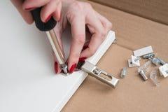 Möbelinstallationen Die Frau schraubt die Schleife zur Seite das d stockbild