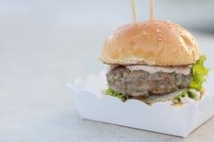 Möbeln Sie Burger- und Majonäsensoßen- und -sesambrötchen serverd auf Papierkasten auf Lizenzfreie Stockbilder