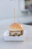 Möbeln Sie Burger- und Majonäsensoßen- und -sesambrötchen serverd auf Papierkasten auf Stockbild