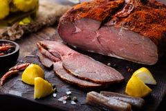 Möbeln Sie die Pastrami auf, die, das gebratene Rindfleisch geschnitten wird, langsam kochend, mariniert in den Olivenölaubergine stockfotos