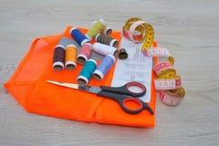 Möblemang och utrustning för att sy i märkes- systuga Instrument som syr upp hantverket på träbakgrundsslut hjälpmedel för Royaltyfri Bild