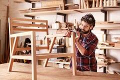 Möblemangformgivare som sandpapprar en trästolram Arkivfoto