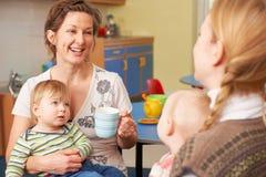 Mödrar med behandla som ett barn att prata och att dricka kaffe på Playgroup arkivfoton