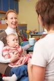 Mödrar med behandla som ett barn att prata på Playgroup royaltyfri fotografi