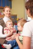 Mödrar med behandla som ett barn att prata på Playgroup arkivfoton